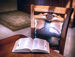 This is an image of an open bible sitting on a table, a chair is pushed back, and the shadow from a nearby window falls across it.